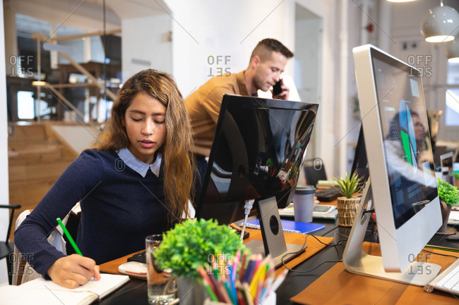 Mixed race female business creative working in a casual modern office, sitting at a desk and taking notes with colleagues working in the background