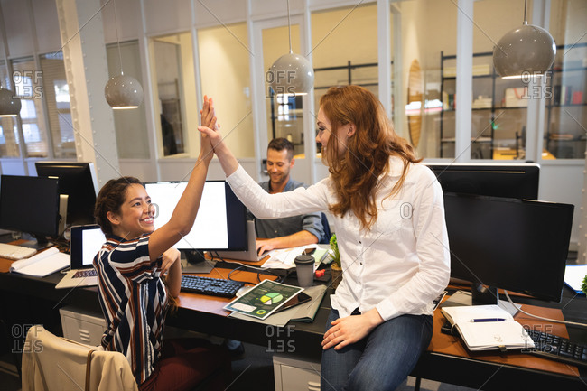 Mixed race female and Caucasian female business creatives working in a casual modern office, sitting at a table, high fiving and smiling