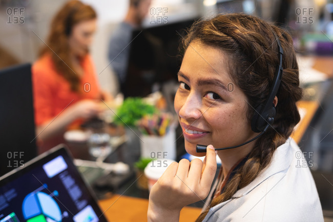Portrait of a happy, mixed race female business creative working in a casual modern office, talking on a phone headset and looking at camera, with colleagues working in the background