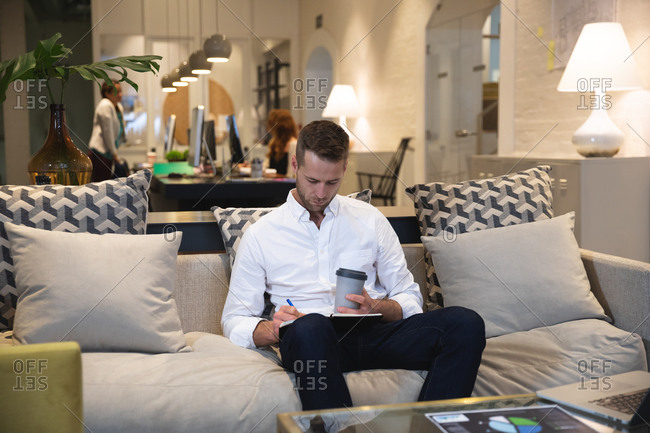 Caucasian male business creative working in a casual modern office, sitting on a sofa drinking a coffee and making notes, with colleagues working in the background