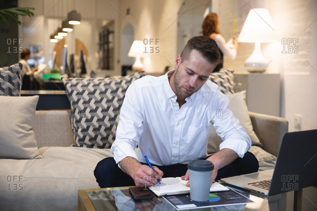 Caucasian male business creative working in a casual modern office, sitting on a sofa and making notes, with colleagues working in the background