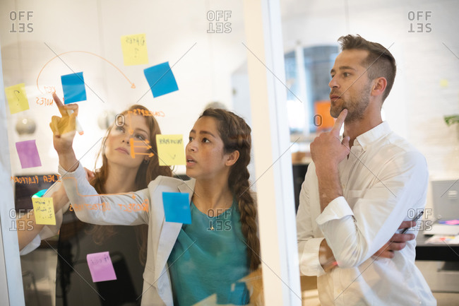 Group of three male and female business creatives working in a casual modern office, standing and writing notes on a glass wall while brainstorming together