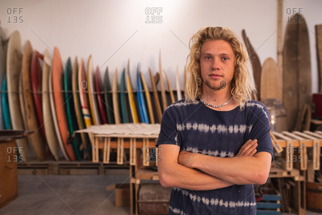 Portrait of a Caucasian male surfboard maker in his studio, with surfboards in a rack in the background, standing with his arms crossed and looking straight to camera.