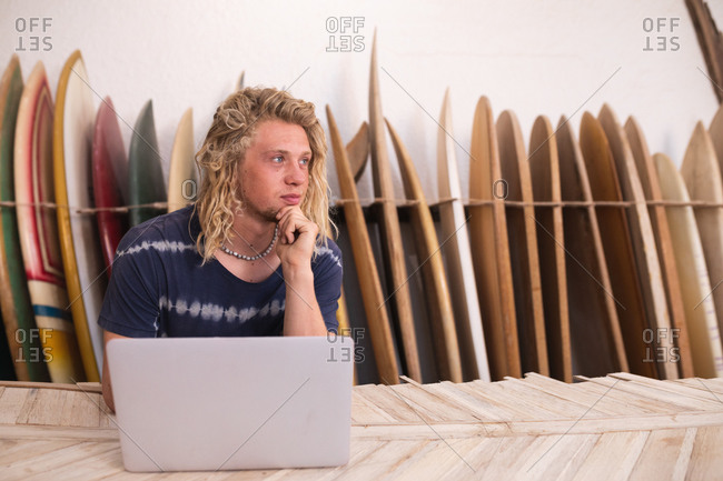 Caucasian male surfboard maker in his studio, working on a project using his laptop, with surfboards in a rack in the background.
