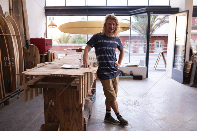 Portrait of a Caucasian male surfboard maker in his studio, with surfboards in a rack in the background, standing by his worktable and looking at camera and smiling.