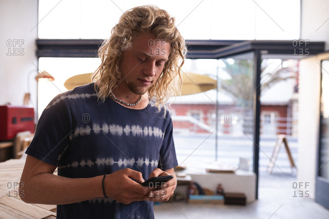 Caucasian male surfboard maker with long blond hair, wearing blue tshirt and wooden jewelry, standing in his studio, using his smartphone.