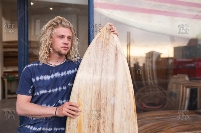 Caucasian male surfboard maker standing in front of his studio, leaning on a door frame of the entrance, holding a brand new surfboard.