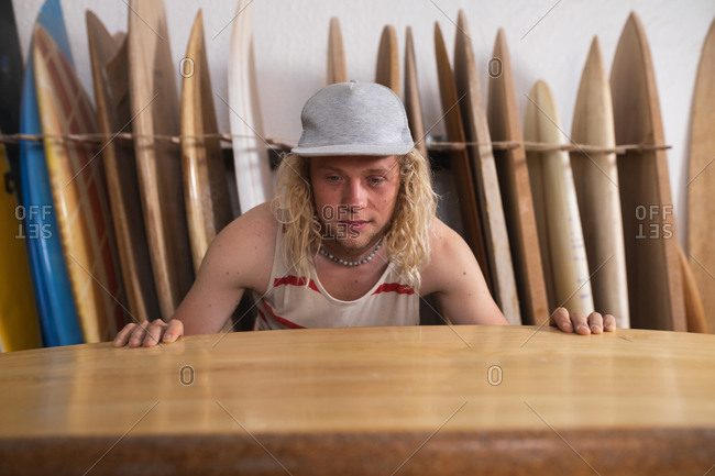 Caucasian male surfboard maker in his studio, inspecting one of the surfboards, with other surfboards in a rack behind him.