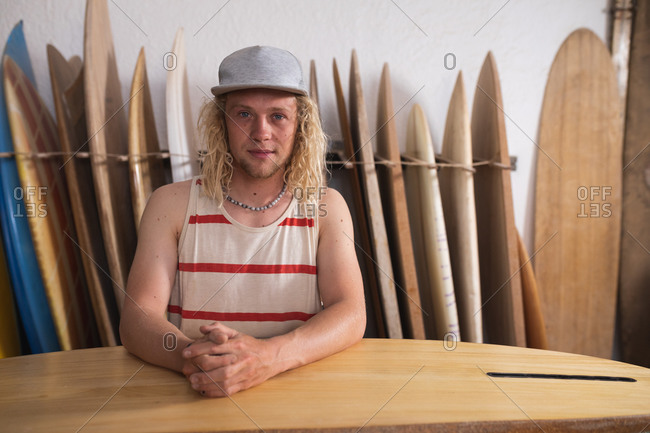 Portrait of a Caucasian male surfboard maker in his studio, holding one of the surfboards and smiling to camera, with other surfboards in a rack in the background.