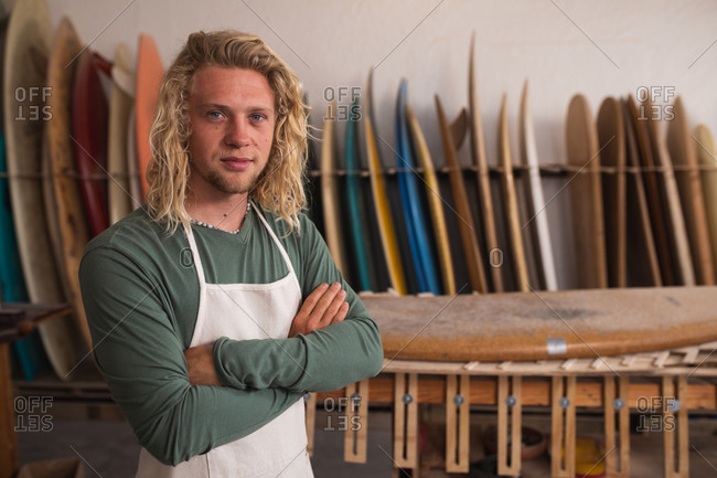 Portrait of a Caucasian male surfboard maker in his studio, standing with his arms crossed, looking at camera and smiling, with surfboards in a rack in the background.