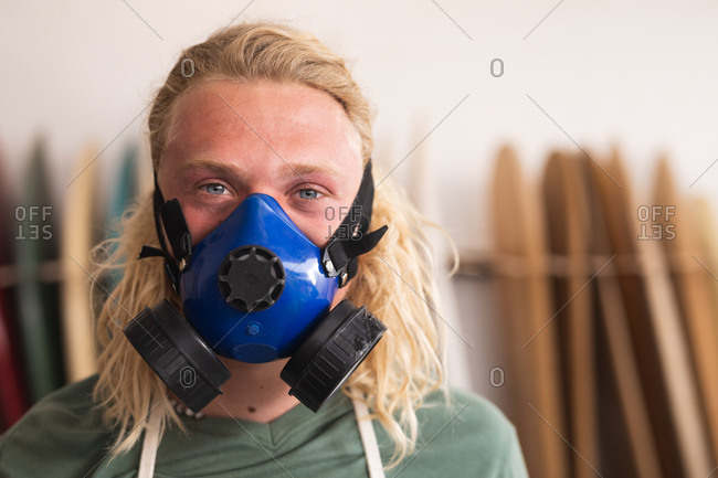 Portrait of a Caucasian male surfboard maker in his studio, wearing a breathing face mask and looking at camera, with surfboards in a rack in the background.