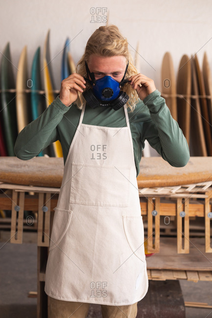 Caucasian male surfboard maker in his studio, putting on a breathing face mask and looking at camera, with surfboards in a rack in the background.