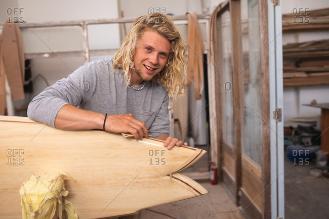 Caucasian male surfboard maker with long blond hair, in his studio, polishing a surfboard, looking at camera and smiling.