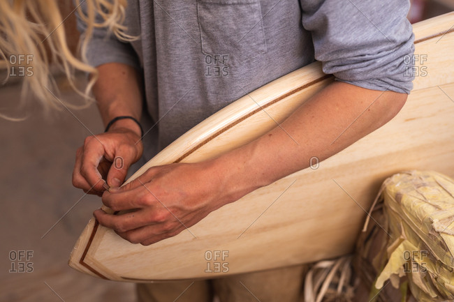 Mid section of a Caucasian male surfboard maker with long blond hair, in his studio, polishing a wooden surfboard edge.