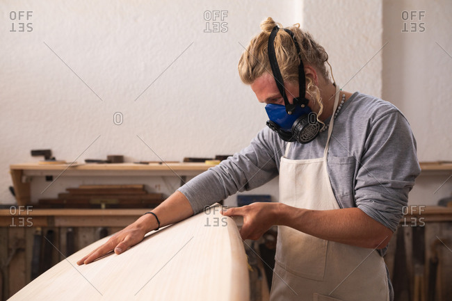 Caucasian male surfboard maker with long blond hair, wearing a face mask, working in his studio, making a surfboard, inspecting it and preparing to polishing..