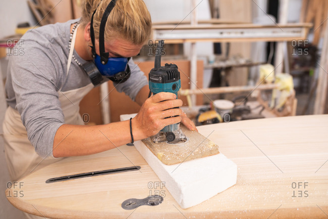 Caucasian male surfboard maker with long blond hair, wearing a face mask, working in his studio, making a surfboard, sanding its surface with a sander.