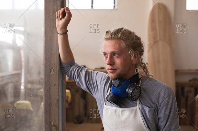 Caucasian male surfboard maker with long blond hair, wearing a face mask, standing in his studio, leaning on a door frame while taking a break during his work.