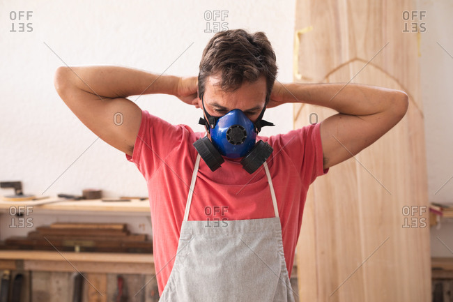Caucasian male surfboard maker working in his studio, wearing a protective apron, putting on a breathing face mask preparing to polishing a surfboard.
