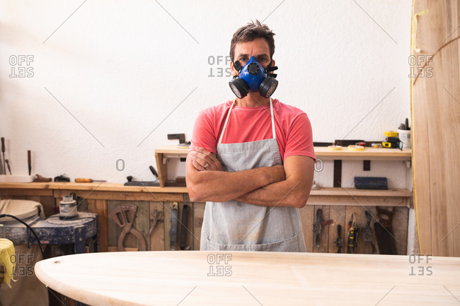 Portrait of a Caucasian male surfboard maker working in his studio, wearing a protective apron and a face mask, standing with his arms crossed and looking at camera.