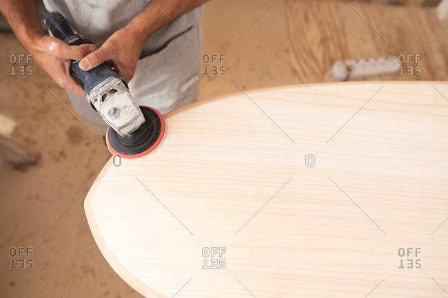 Mid section of a Caucasian male surfboard maker working in his studio, wearing a protective apron, shaping a wooden surfboard with a sander.