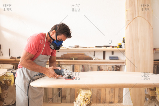 Caucasian male surfboard maker working in his studio, wearing a protective apron and a breathing face mask, shaping a wooden surfboard with a sander.