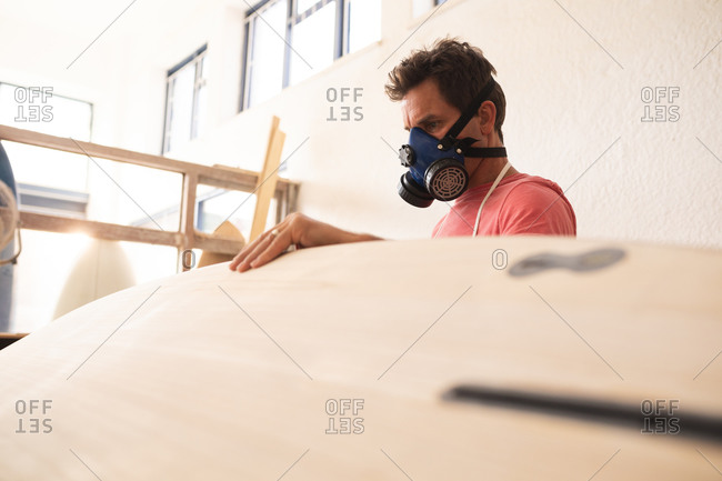 Caucasian male surfboard maker working in his studio, wearing a protective apron and a breathing face mask, inspecting a wooden surfboard during shaping it with a sander.