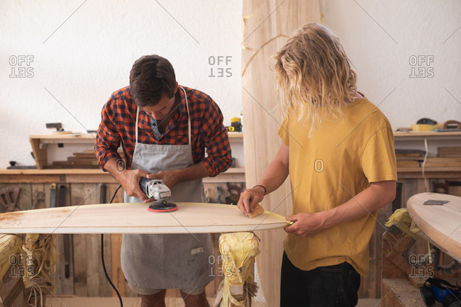 Two Caucasian male surfboard makers working in their studio and making a wooden surfboard together, polishing and shaping it with a sander.