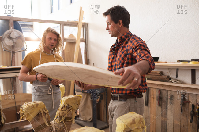 Two Caucasian male surfboard makers working in their studio and making a wooden surfboard together, inspecting it before painting the surface.