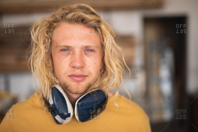 Portrait of a Caucasian male surfboard maker with long blond hair, standing in his studio, wearing protective headphones and looking at camera.