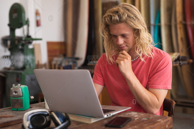 Caucasian male surfboard maker working in his studio, sitting at desk and using his laptop computer, with surfboards in a rack in the background