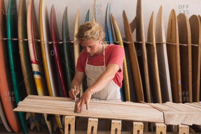 Caucasian male surfboard maker working in his studio, cutting wooden stripes and preparing to make a surfboard, with surfboards in a rack in the background