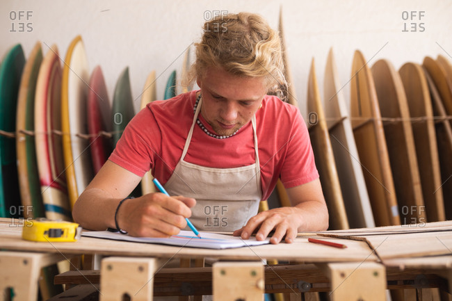 Caucasian male surfboard maker working in his studio, drawing surfboards projects in a sketchbook,  with surfboards in a rack in the background.