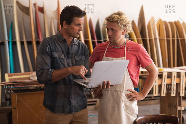 Two Caucasian male surfboard makers working in their studio, standing by the door frame and working on projects using a laptop computer, with surfboards in the background