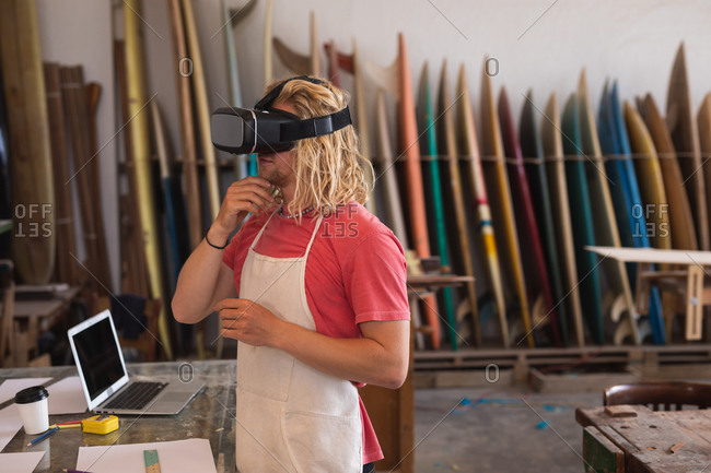 Caucasian male surfboard maker working in his studio, using a VR headset, with surfboards in a rack in the background.