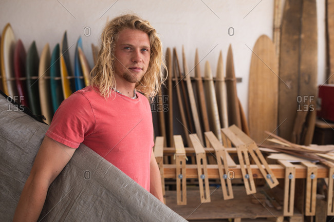 Caucasian male surfboard maker working in his studio, holding a surfboard covered with a grey case, with surfboards in a rack in the background.