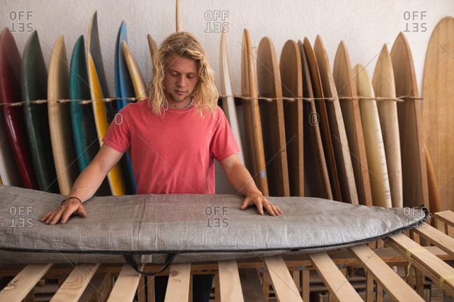 Caucasian male surfboard maker working in his studio, inspecting a surfboard covered with a grey case, with surfboards in a rack in the background.