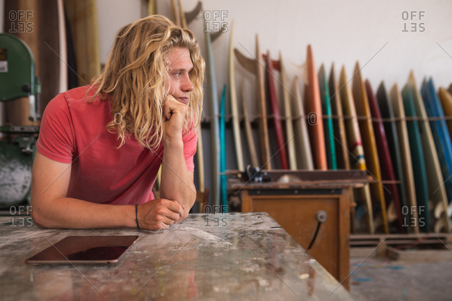 Thoughtful Caucasian male surfboard maker working in his studio, leaning on a counter and touching his chin, using a tablet computer, with surfboards in a rack in the background