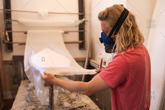 Caucasian male surfboard maker wearing a breathing face mask, working in his studio, inspecting a surfboard covered with a white piece of cloth.