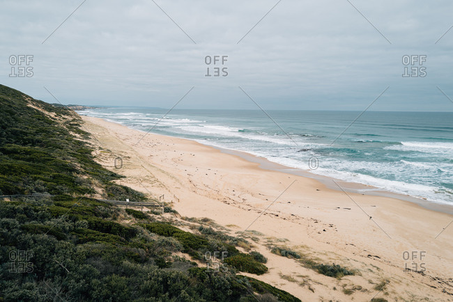 Waves rolling into a sandy beach on a cloudy day