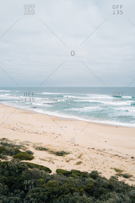 Waves rolling into a beach on a cloudy day
