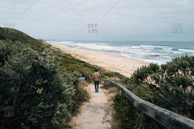 Man walking down path towards a beach on a cloudy day