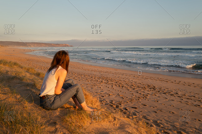 Woman sitting on beach overlooking waves at sunset