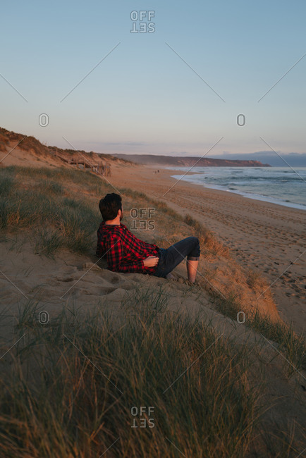 Man sitting on beach overlooking waves at sunset