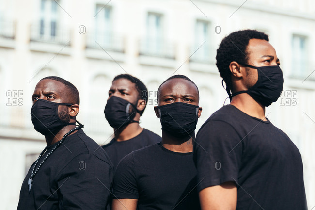 Black men on street holding masks. One of the is looking at camera with serious expression