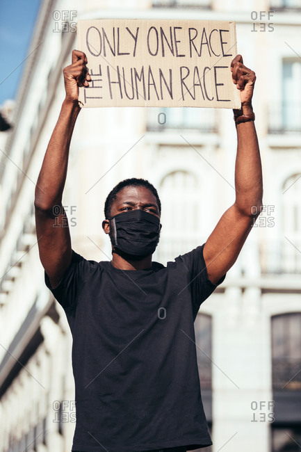 Man crying and protesting at a rally for racial equality holding a poster against racism. Black Lives Matter.
