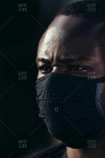 Closeup portrait of african american man wearing a black mask. He is looking away with serious expression