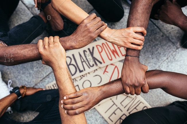 Anonymous black people holding arms as a gesture against racism