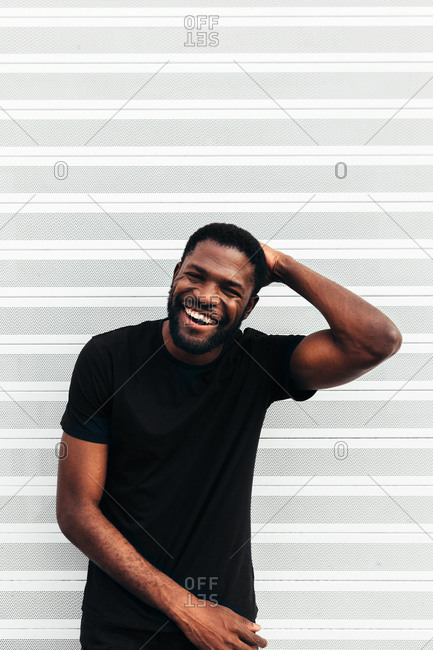 Happy black man posing and smiling over white background