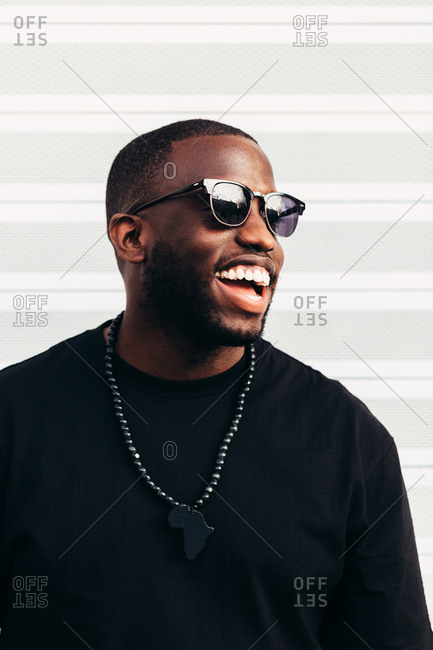 Happy black man posing and smiling over white background and wearing black sunglasses