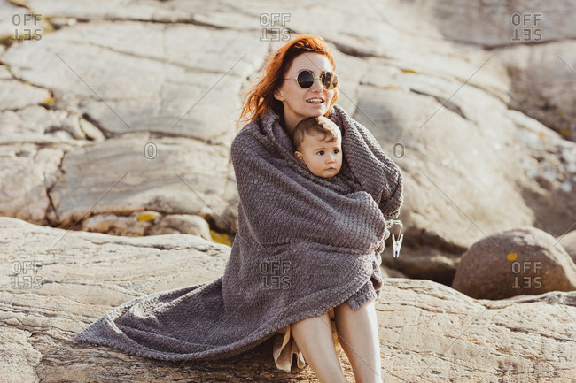 Mother and baby girl wrapped in blanket while sitting on rock formation during summer